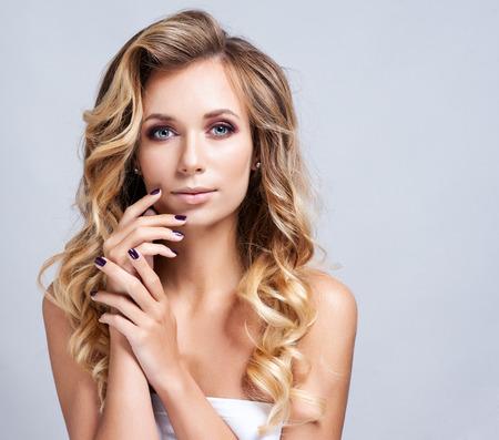 visage profil: Portrait d'une femme belle blonde avec coiffure bouclée et maquillage lumineux. Aspect naturel. atelier, isolé. Banque d'images