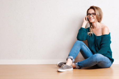 Portrait of a smiling woman sitting on the floor and talking on the phone on gray background