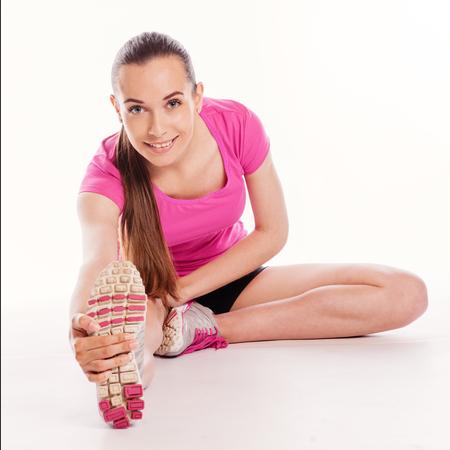 warm up: Donna adatta che allunga il suo piedino per riscaldare - isolato su sfondo bianco