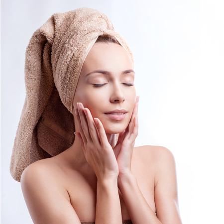 Spa pielęgnacja skóry piękna kobieta ubrana ręcznikiem włosy po zabiegu kosmetycznym. Piękny wielorasowe młoda kobieta z doskonałej skóry na białym tle. Zdjęcie Seryjne