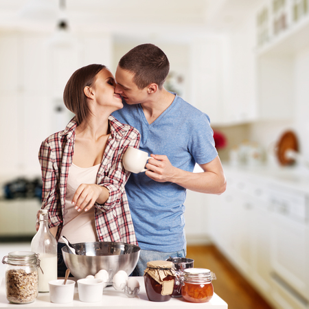 pareja de esposos: Hombre cariñoso que besa a su novia mientras se corta el pan para el desayuno en la cocina