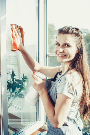 cleanser: people, housework and housekeeping concept - happy woman in gloves cleaning window with rag and cleanser spray at home.
