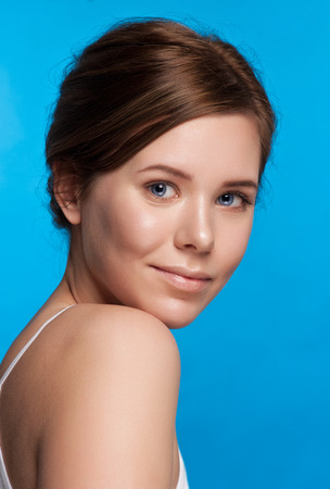 aging: Beautiful face of young adult woman with clean fresh skin - isolated on blue. Stock Photo