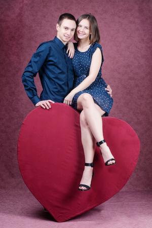 parejas enamoradas: hermosa joven pareja abrazando en frente de un corazón enorme.
