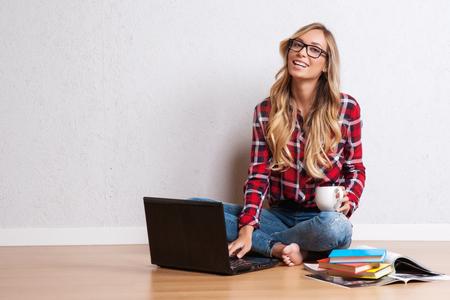 mujer sentada: Mujer creativa joven que se sienta en el suelo con el portátil.  Mujer blogger ocasional Foto de archivo