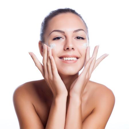 bella modelo de aplicar el tratamiento crema cosmética en la cara en blanco Foto de archivo