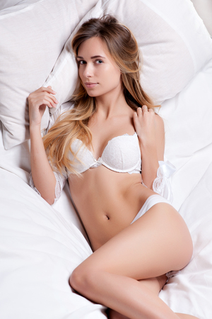 High fashion look.glamor closeup portrait of beautiful sexy stylish young woman model lying on white bed