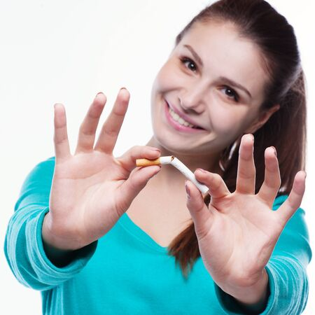 quit smoking: Young happy woman with broken cigarette. Stop smoking concept.