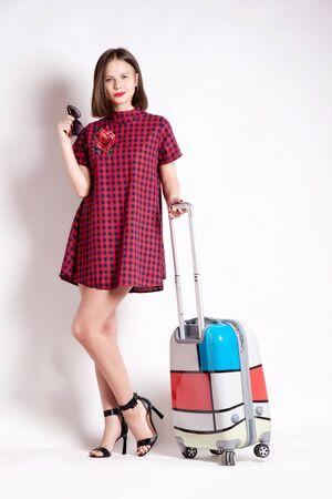 femme valise: Longueur totale de la femme décontractée debout avec une valise de Voyage - isolé sur fond blanc