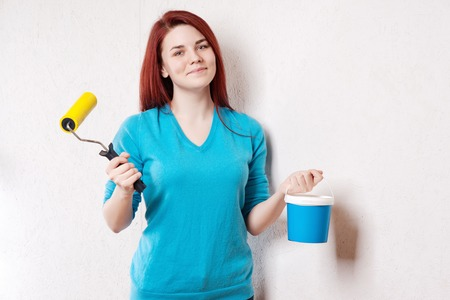 causal: Beautiful young woman in causal clothes enjoying the result of the work she has done painting a wall.