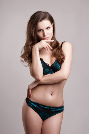 femme brune sexy: femme sensuelle posant en noir lingerie sexy tout en isolé Banque d'images