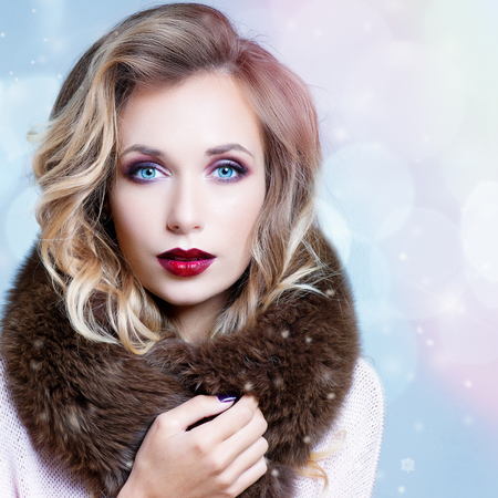 Winter Woman in Luxury Fur Coat. Beauty Fashion Model Girl in Blue Fox Fur Coat. Perfect Makeup, accessories and hairstyle. Beautiful Luxury Winter Lady