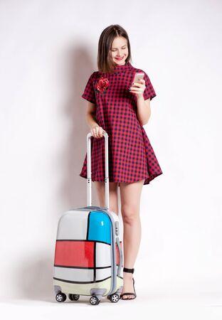 valise voyage: Longueur totale de la femme décontractée debout avec une valise de Voyage - isolé sur fond blanc