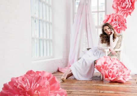 Mooi sexy meisje in een lange jurk met een enorme roze bloemen zat bij het raam. Stockfoto