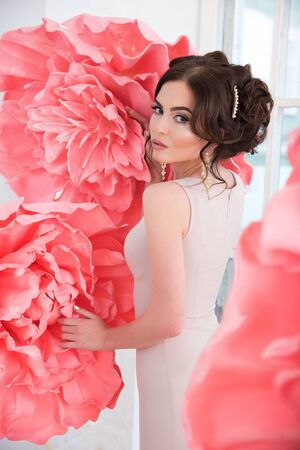 dress up: Beautiful sexy girl in a long dress with a huge pink flowers sitting by the window.
