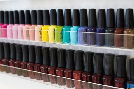 Set of different nail varnishes on shelves in cosmetic store.