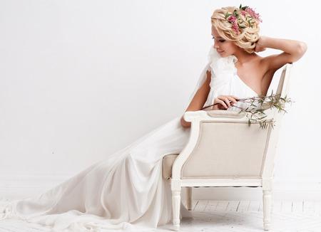 Belle mariée avec le bouquet sur fond blanc
