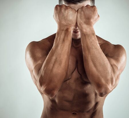 Two Power Mans Hands in Front of Face. Close-up of a mans fists and abs. Strong mans arm with muscles and veins. Stock Photo