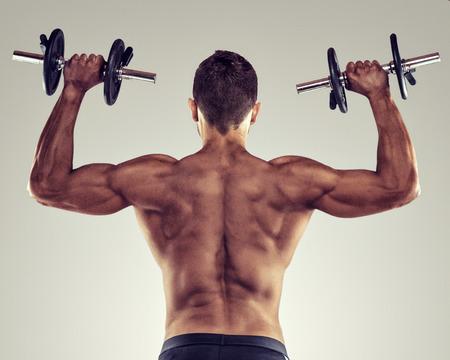 Rückansicht eines jungen männlichen Bodybuilder tun schweres Gewicht Übung mit Hanteln.