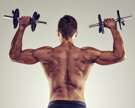 Rear view of a young male bodybuilder doing heavy weight exercise with dumbbells.