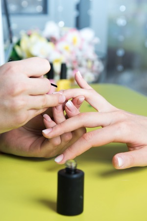 nailcare: Closeup shot of a woman in a nail salon receiving a manicure by a beautician with nail file. Woman getting nail manicure. Beautician file nails to a customer.