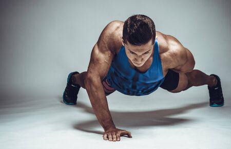 fitness hombres: joven atleta fuerte haciendo flexiones sobre una mano. Concepto de deportes. Foto de archivo