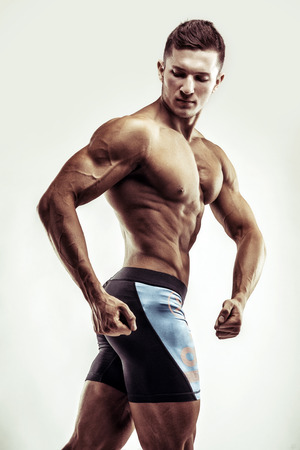 fit: Bodybuilder man posing, showing perfect abs, houlders, biceps, triceps, chest. Stock Photo
