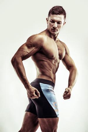 Kulturysta mężczyzna stwarzających, wykazujące doskonałą abs, houlders, biceps, triceps, klatkę piersiową. Zdjęcie Seryjne