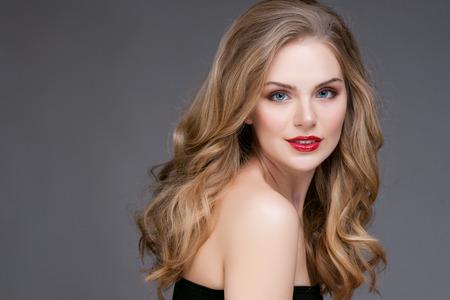 Portret van mooie blonde vrouw met krullend kapsel en lichte make-up. Natuurlijke uitstraling. studio, geïsoleerd.