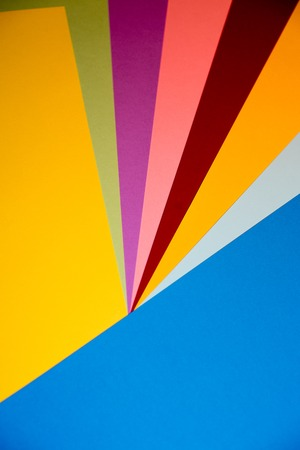Color papers geometry flat composition background with yellow orange red violet and blue tones. Stock Photo