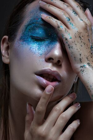 glitter makeup: vivid portrait of a girl with an unusual blue make-up.