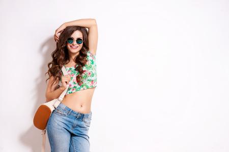 moda: mulher do estudante moderno legal que veste óculos de eyewear. estudante universitário fêmea caucasiano que olha a câmera sorrindo feliz. Banco de Imagens