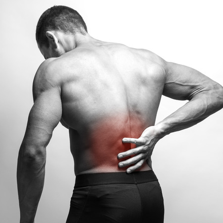 soreness: Male athlete with pain in his lower back, isolated in grey. Red spot around painful area.