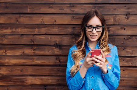 美しい若い流行に敏感な女性がスマート フォンを使用します。