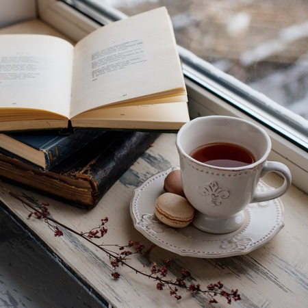 warm drink: Cozy winter still life: cup of hot coffee and opened book on vintage windowsill against snow landscape from outside.