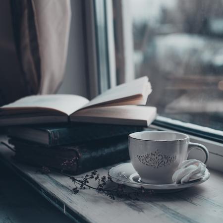 Gezellig winter stilleven: kopje warme koffie en geopend boek op vintage vensterbank tegen sneeuwlandschap van buitenaf.