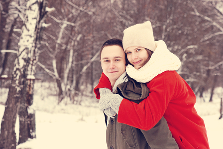 couples hug: Embracing couple looking at camera with smiles in winter park. Stock Photo