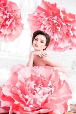 Mooi sexy meisje in een lange jurk met een enorme roze bloemen zat bij het raam.