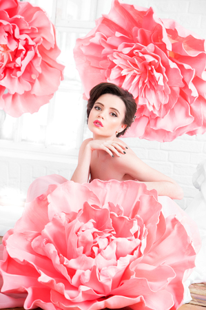 Beautiful sexy girl in a long dress with a huge pink flowers sitting by the window.