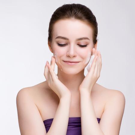 Retrato de rostro de mujer de belleza. Hermosa chica modelo Spa con perfecta piel limpia fresca. Mujer mirando a cámara y sonriendo. Foto de archivo