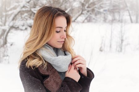 Beautiful winter portrait of young woman in the winter snowy scenery. photo