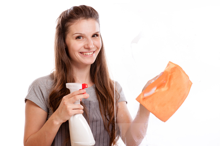 people, housework and housekeeping concept - happy woman in gloves cleaning window with rag and cleanser spray at home.