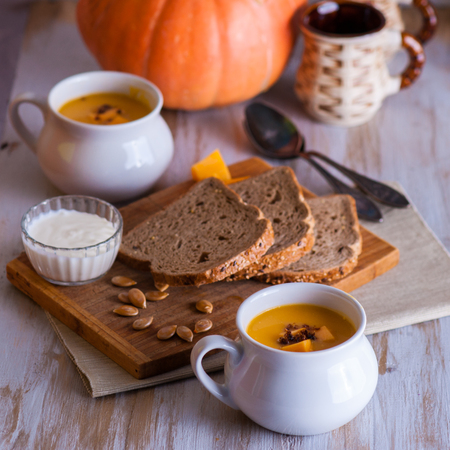 Roasted pumpkin and carrot soup with cream and pumpkin seeds on white wooden background. Copy space. Stock Photo