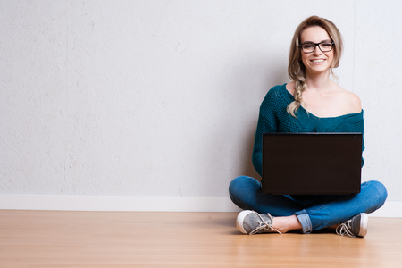 Young creative woman sitting in the floor with laptop. Casual blogger woman photo