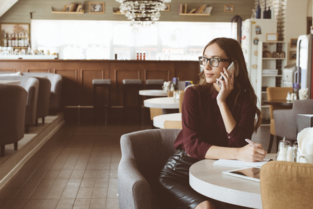 Une femme à la cafétéria parle au téléphone. Banque d'images - 81148096
