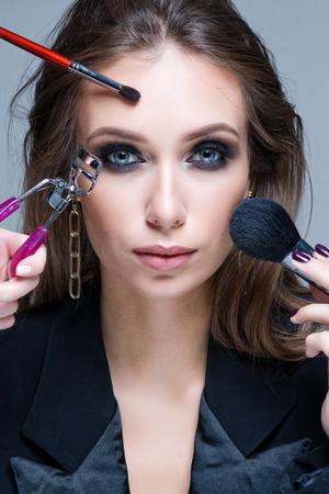 Beautiful Fashion Luxury Makeup, long eyelashes, perfect skin facial make-up. Beauty Brunette model woman holiday make up close up. Eyelash extensions, false eyelashes. Stock Photo