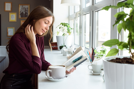 electronic commerce: Charming woman with beautiful smile reading good news on mobile phone during rest in coffee shop, happy Caucasian female watching her photos on cell telephone while relaxing in cafe during free time.