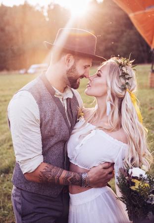 Mooi jong stel in trouwjurken in Bohho-stijl, op een veld met een ballon. Stockfoto
