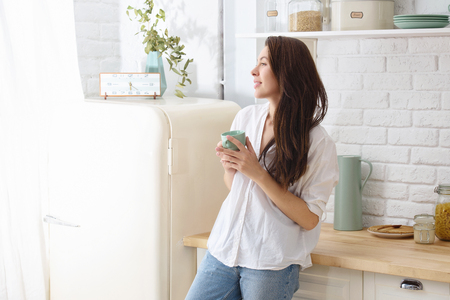 Young happy woman drinking coffee on the kitchen in the morning. Stockfoto