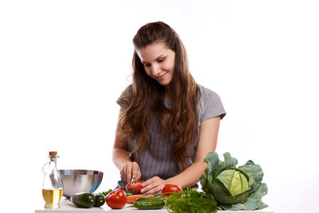 happy adult woman with various fresh vegetables on kitchen table looking at camera.